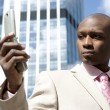 Close up of a businessman using a cell phone in the financial district. — Stock Photo