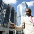 Stock Photo: Businessman using a cell phone while standing in the financial district.