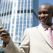 Successful businessman using a cellular phone in the city. — Stock Photo