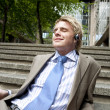 Young businessman listening to music with headphones while sitting down on some steps in the city. — Stock Photo