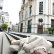 Stock Photo: Homeless businessmsleeping outdoors in financial district.