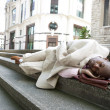 Homeless businessman sleeping outdoors in the financial district. — Stock Photo