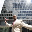 Businessman throwing boomerang while standing in the middle of the financial district. — Stock Photo