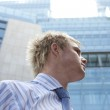 Low view of a businessman standing by office buildings in the city. — Stock Photo #21738645