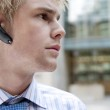 Young businessman using a hands free device to speak on his cell phone — Stock Photo #21738695