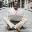 Young businessman using a laptop computer while sitting in the middle of the road. — Stock Photo