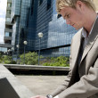 Young businessman typing on a laptop computer while sitting by modern office building. — Stock Photo