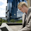 Young businessman typing on a laptop computer while sitting by modern office building — Stock Photo