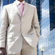Young businessman standing by reflective office building. — Stock Photo #21738833
