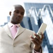 Detail of a cell phone being used by a businessman in the financial district. — Stock Photo #21738851
