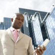 Businessman using a cell phone, standing by a reflective office building. — Stock Photo