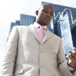Businessman using a cell phone, standing by a reflective office building. — Stock Photo #21738869