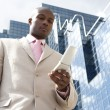 Businessman using a cell phone, standing by a reflective office building. — Stock Photo #21738879