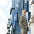 Two businessmen standing by a modern office building. - Foto de Stock