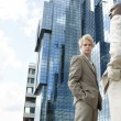 Two businessmen standing by a modern office building. - Lizenzfreies Foto