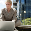 Businessman sitting down by an office building, using his laptop. — Stock Photo