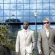 Two businessmen decisively walking by a glass office building. — Stock Photo