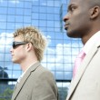 Two businessmen walking by a reflective office building in the city. — Stock Photo #21739147