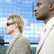 Two businessmen walking by a reflective office building in the city. — Stock Photo