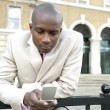 Young businessman texting on a cell phone in the city. — Stock Photo
