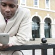 Businessman texting on a cell phone outdoors — Stockfoto