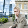 Young businessman leaning on a banister in the city - Stock Photo