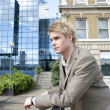 Young businessman leaning on a banister in the city — Stock Photo