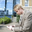 Businessman texting on a cell phone outdoors — Stock Photo