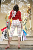 Back view of a young woman standing by a shop window, holding shopping bags. — Stock Photo