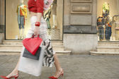 Young woman walking by a shop window, with shopping bags. — Stock Photo