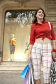 Young woman holding shopping bags, standing by shop window. — Stock Photo