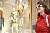 Portrait of a fashionable young woman looking at a shop window. — Stock Photo