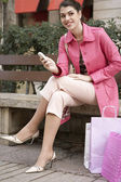 Young woman sitting down on a bench with her shopping bags — Stock Photo