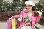 Young woman holding her pearl necklace while sitting down with shopping bags. — Stock Photo