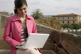 Young woman using a laptop outdoors, while on vacation. — Stock Photo