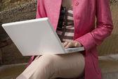 Jeune femme à l'aide d'un ordinateur portable à l'extérieur. — Photo