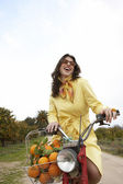 Elegant young woman riding a motorbike in an orange grove. — Stock Photo