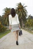 Elegante giovane donna percorrendo un sentiero di campagna con palme. — Foto Stock