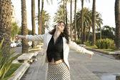 Joven mujer caminando negligentemente en la ciudad con sus brazos extendidos en el aire — Foto de Stock