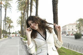 Attractive woman talking on a cell phone in a tree aligned street — Stock Photo