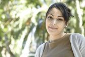 Jonge vrouw met groene gebladerte op de achtergrond. — Stockfoto