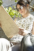 Young businesswoman reading a financial newspaper in a park — Stock Photo