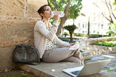 Beautiful young woman having her lunch break in a city park — Stock Photo