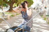 Attractive young woman using the mirrors on her motorbike — Stock Photo