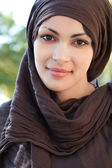 Muslim young woman wearing a head scarf and smiling at the camera — Stock Photo