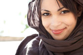 Beauty portrait of a muslim young woman wearing a head scarf and smiling at the camera — Stock Photo