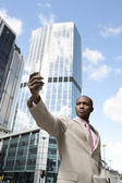 Businessman holding a cell phone while standing in the financial district. — Stock Photo