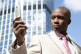 заделывают бизнесмена, используя мобильный телефон в центре финансового района. — Стоковое фото