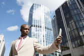 Businessman using a cell phone while standing in the financial district. — Stock Photo