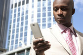 Businessman using a cell phone in the financial district. — Stock Photo